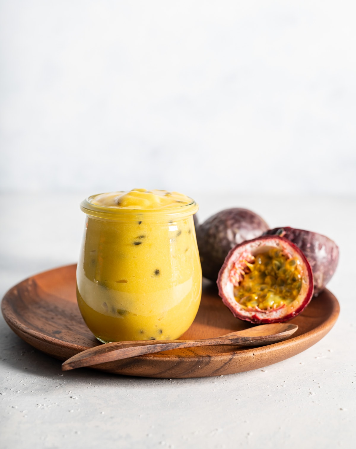 yellow passion fruit curd in a jar with fresh passion fruits cut in half brown plate