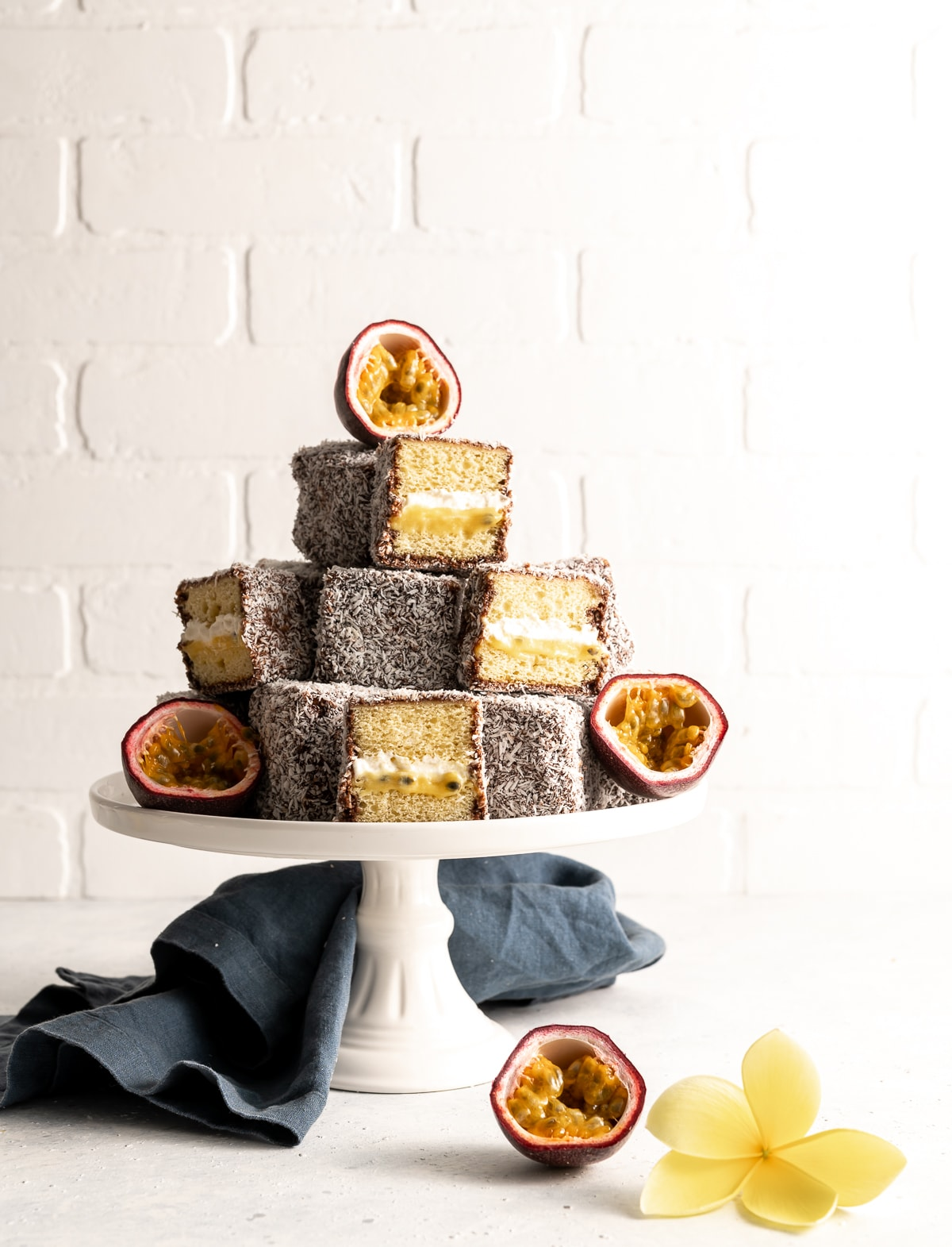 tower of lamingtons on a cake plate some whole some cut in half fresh passion fruit cut in half