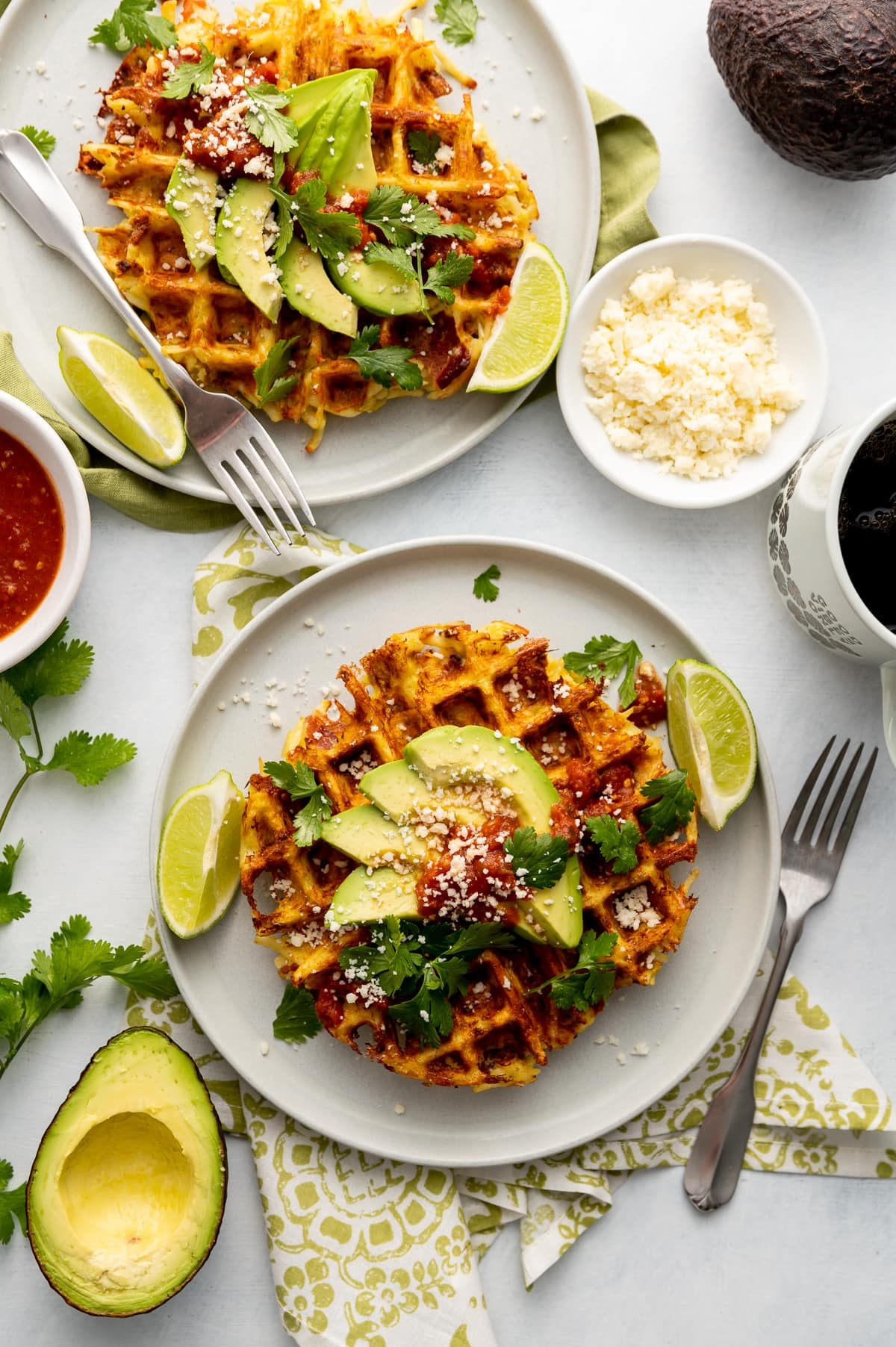 savory hash brown waffles with avocado slices lime slices whole and half avocados on white plates