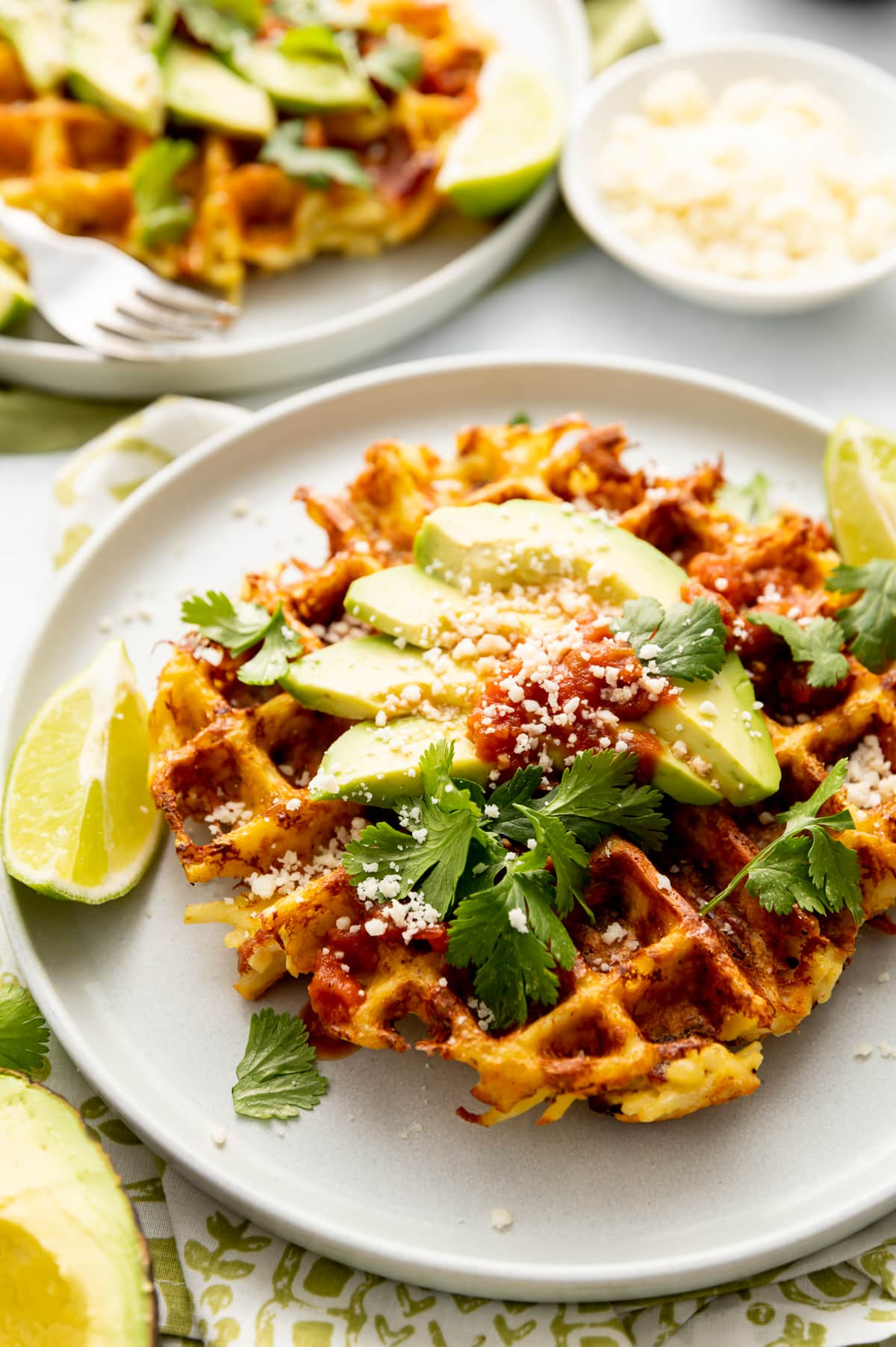 hash brown waffles on white plate with lime slices white crumbled cheese avocado slices cilantro